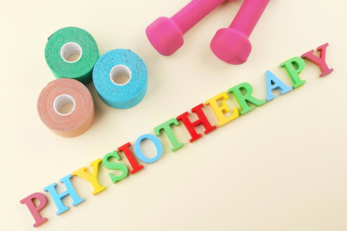 Word physiotherapy with elastic bandage and dumb-bells on beige background
